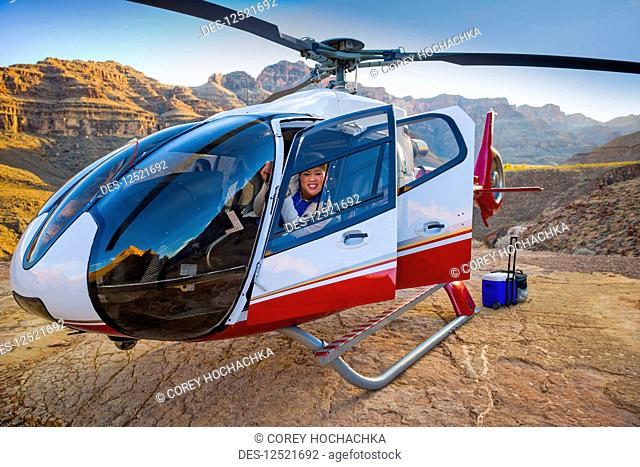 Woman posing in a landed helicopter on a Grand Canyon scenery tour; Las Vegas, Nevada, United States of America
