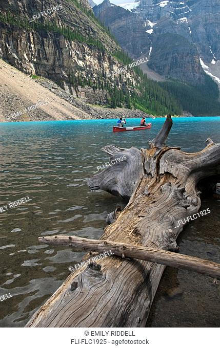 Man and woman paddle canoe in the Valley of the Ten Peaks on Moraine Lake, Lake Louise, Alberta, Canada