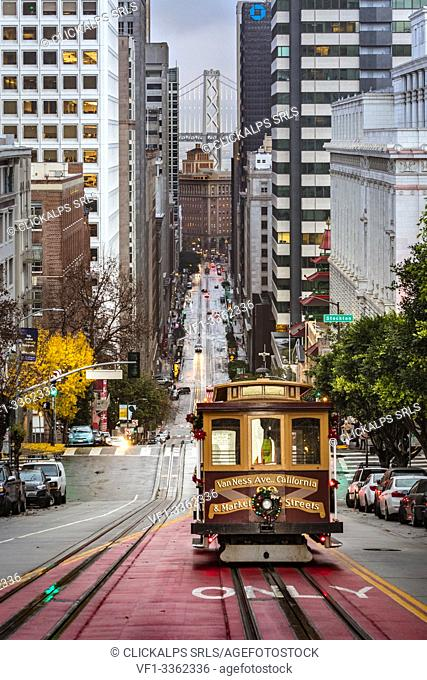 A cable car on California street, with financial district on the background, San Francisco, California, United States Of America