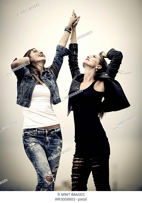 Two young women standing on a rooftop with their arms raised