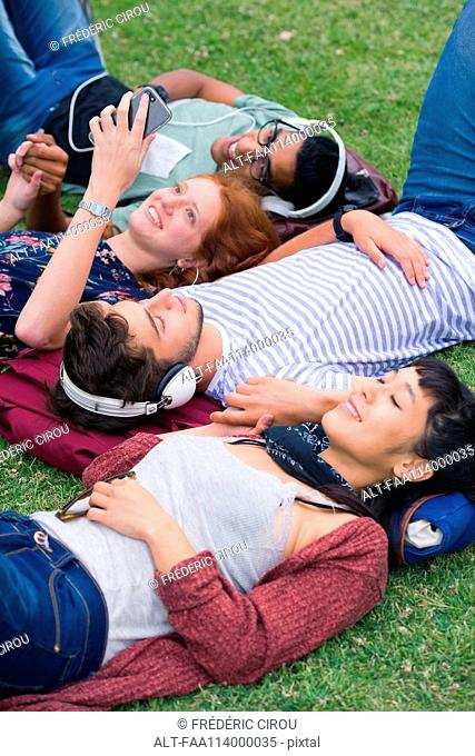 Group of friends lying on grass relaxing together