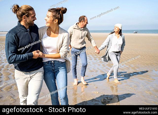 Smiling young couple walking with mature couple in background at beach