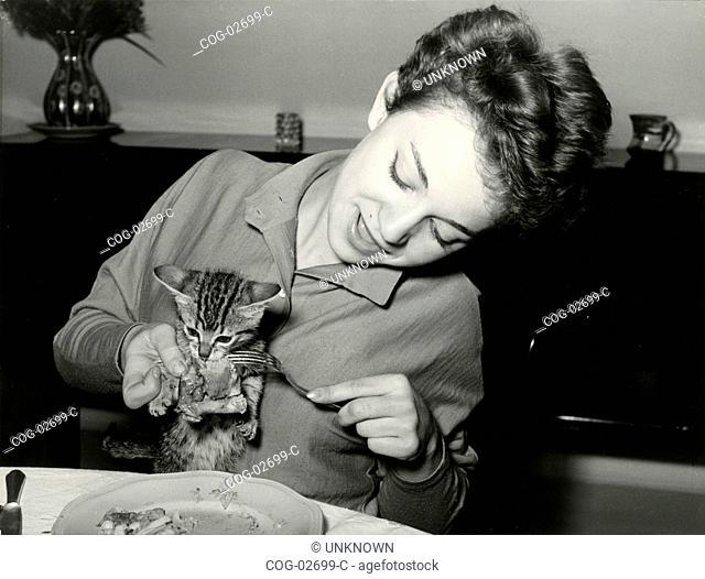 Italian actress Brunella Bovo feeds a kitten at the table