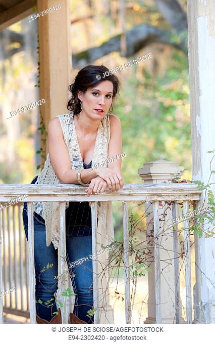36 year old brunette woman outdoors standing on a porch of an old house looking directly at the camera