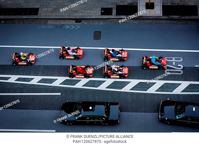 """Bird's eye view of """"""""MariCARs"""""""" roaming a street in the fancy shopping district Ginza, in April 2019. MariCARs resemble Mario Karts but may not be called Mario..."""