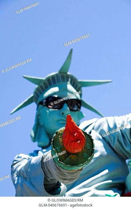 Low angle view of a mid adult man dresses as the Statue of Liberty, New York City, New York State, USA