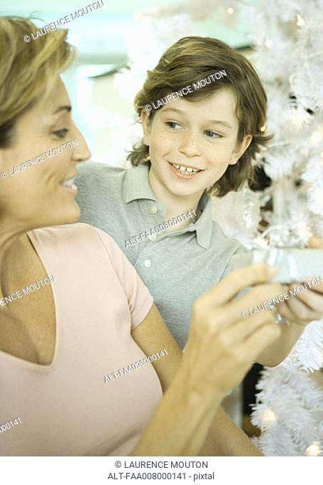 Boy handing mature woman present next to Christmas tree
