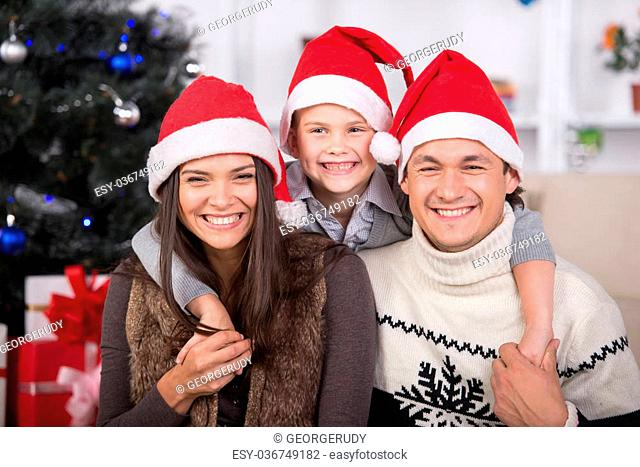 Happy parents and son in Santa hat are looking at camera. Christmas time