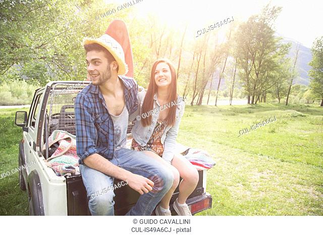 Young couple sitting on back of pick-up truck, Piemonte, Italy