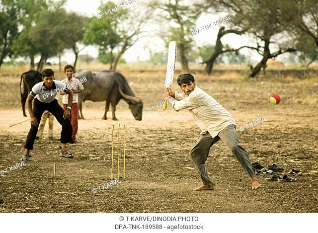 boys playing cricket in farm Salunkwadi Maharashtra India Asia MR#TNK001