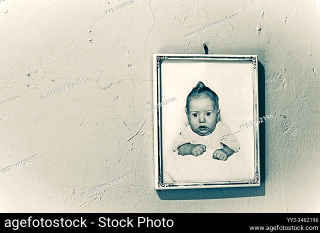 Framed baby picture from the 1950s hanging on the wall