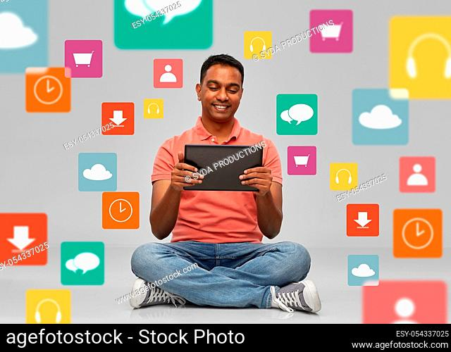 happy indian man with tablet pc over app icons