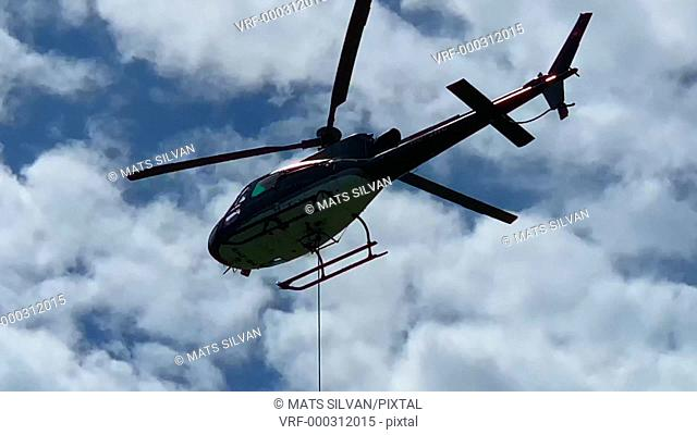 Helicopter Transport Tree Trunk Flying Against Blue Sky and Clouds in Switzerland
