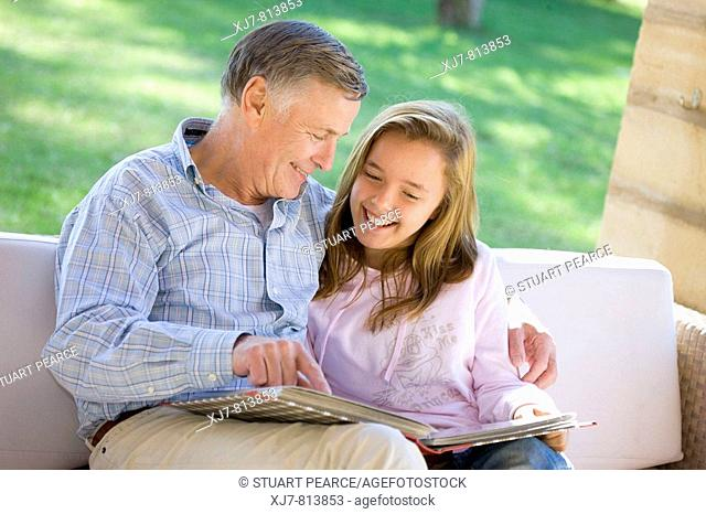 Grandfather and granddaughter looking at photo album