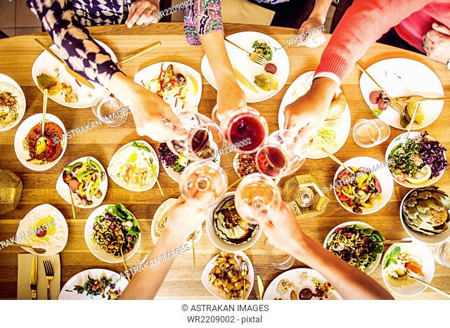 High angle view of friends toasting wineglasses while having meze at table in Lebanese restaurant