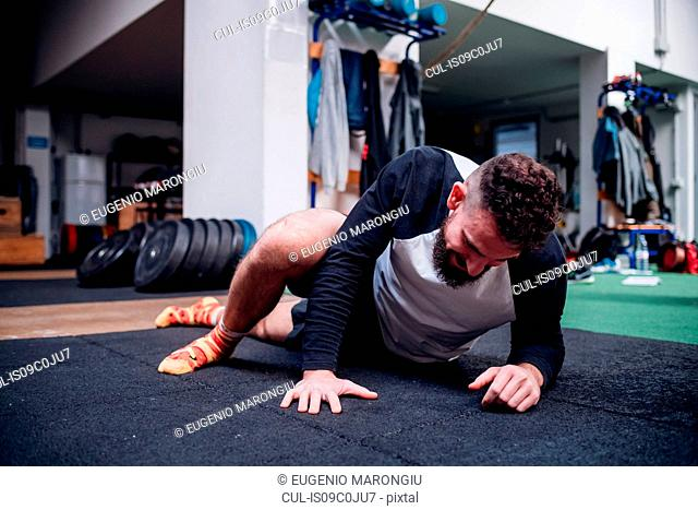 Young man stretching legs in gym