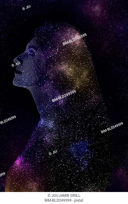 Double exposure of Caucasian woman and stars in outer space