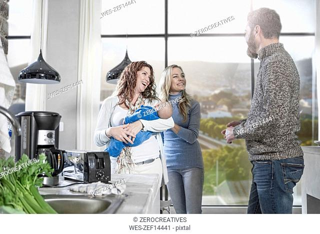 Mother holding baby with friends at home cooking visit