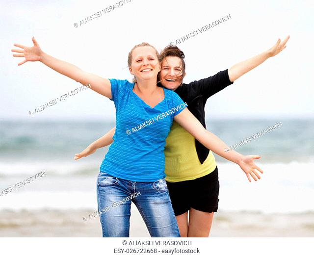 Two happy women on the beach with open arms enjoying their freedom. Shallow depth of field