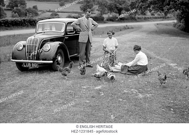 A family group feed chickens beside their car in the countryside, c1945-c1965
