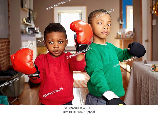 Black boys posing with boxing gloves in living room