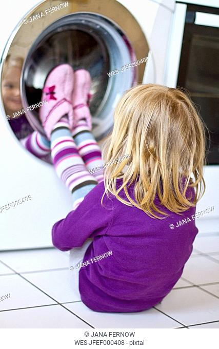 Little girl watching washing machine