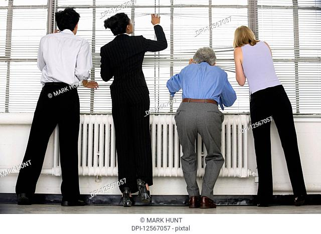 Business executives looking through blinds