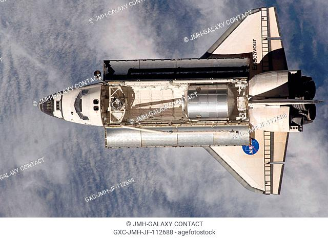 Backdropped by a blue and white Earth, Space Shuttle Endeavour approaches the International Space Station during STS-126 rendezvous and docking operations