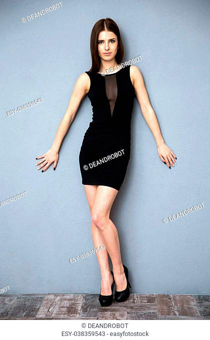 5966bb66c4e Full length portrait of a cute woman in hot dress leaning on the wall