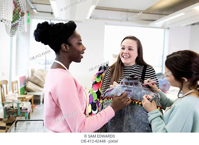 Teenage girls designing denim jacket in fashion design class
