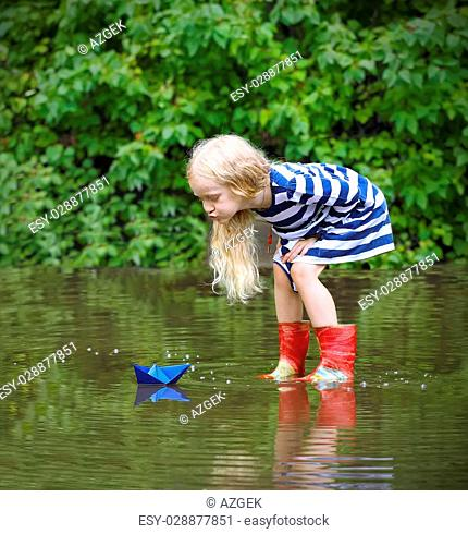 Girl with blue paper boat in a puddle after the rain, summer