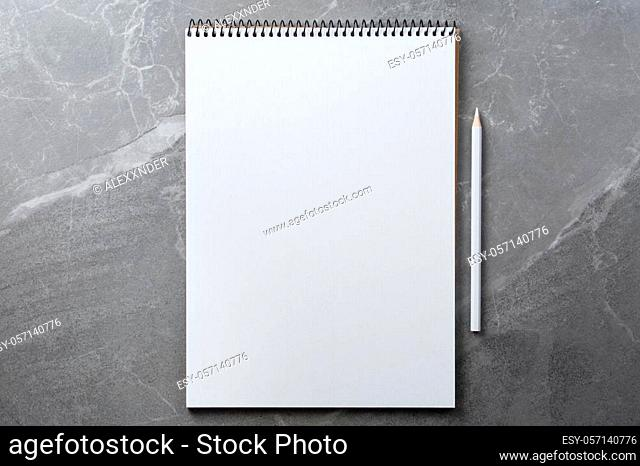 open notebook with white pencil on marble background top view, school notepad on a dark table, office desk flat lay