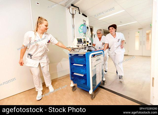 Geriatric hospital ward. Nurses running through the hall of a hospital geriatric ward with a trauma crash cart