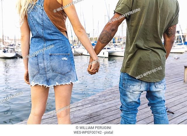 Back view of multicultural young couple standing hand in hand on jetty, partial view