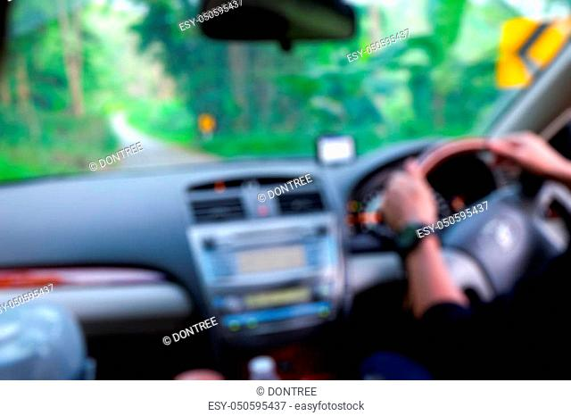 Blur Travel of driver's hands on steering wheel inside of a car