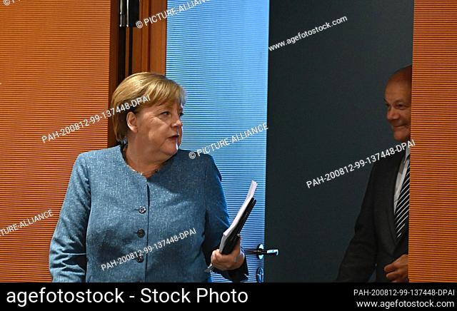 12 August 2020, Berlin: Chancellor Angela Merkel (l, CDU) joins Olaf Scholz (SPD), Federal Minister of Finance, at the meeting of the Federal Cabinet in the...