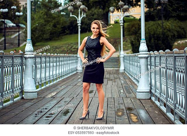 Outdoor lifestyle portrait of blonde young woman in stylish black dress staying on bridge on the street. Autumn, rainy day. Kyiv