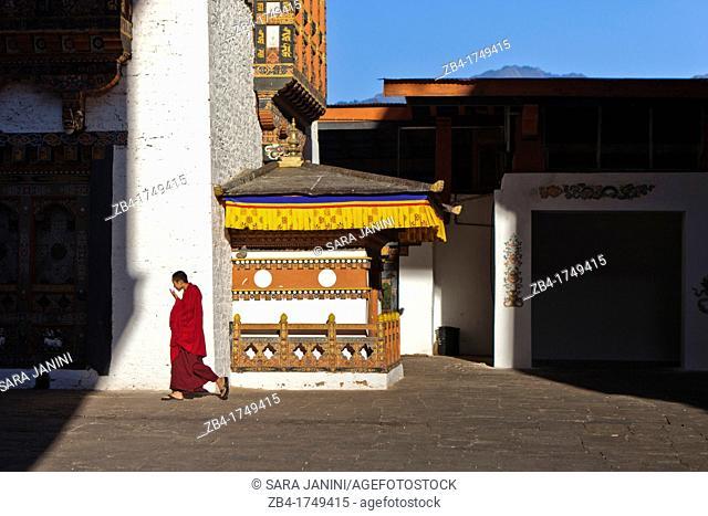 A buddhist monk walking through Punakha Dzong, Punakha, Bhutan, Asia