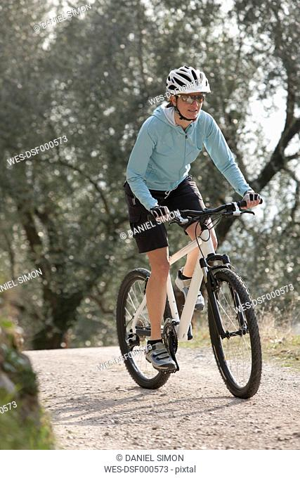 Italy, Trento, Mid adult woman cycling through dirt track