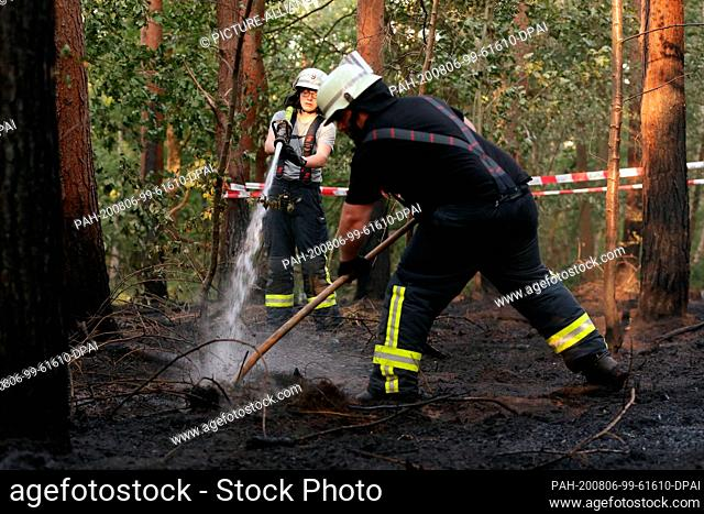 "06 August 2020, North Rhine-Westphalia, Dormagen: Firefighters fight a forest floor fire in the nature reserve """"Zonser Heide"""" with water and pitchfork"