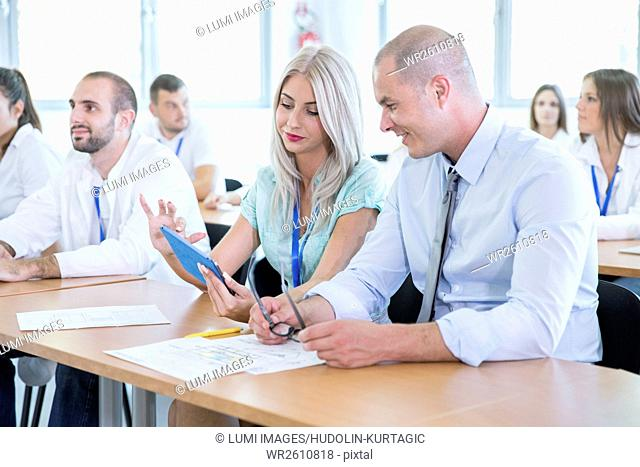 Businessman and woman using tablet in training class