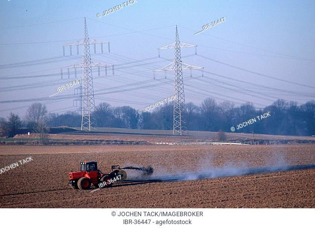 DEU, Germany: Electricall Powerlines.Farmer fertilizes a field