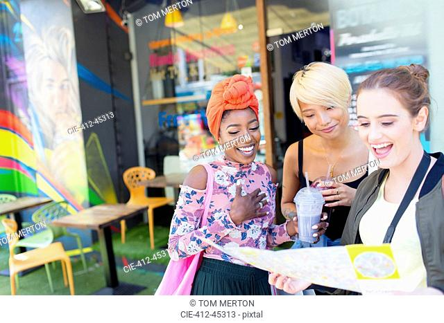 Young women friends with map outside smoothie shop