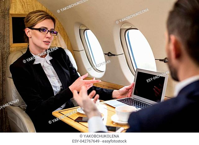 Portrait of peaceful beautiful woman in airplane talking to colleague sitting in front of her and is pointing at her notebook