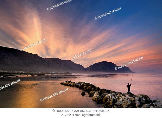 Landscape photo of an amazing sunset over the old harbour on a calm winter evening. Bettys Bay, Western Cape, South Africa