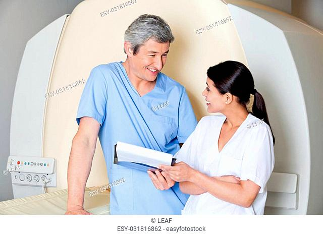 Multiethnic radiologic technicians smiling at each other while standing by MRI scan machine