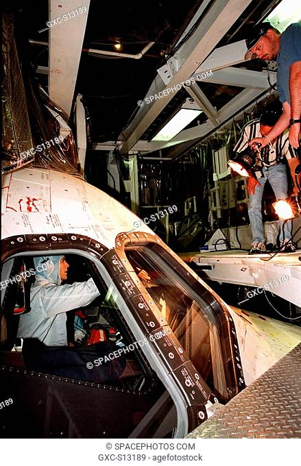 03/24/1999 --- STS-96 Pilot Rick Douglas Husband checks the windows of the orbiter Discovery in the Orbiter Processing Facility bay 1 as a worker shines a light...
