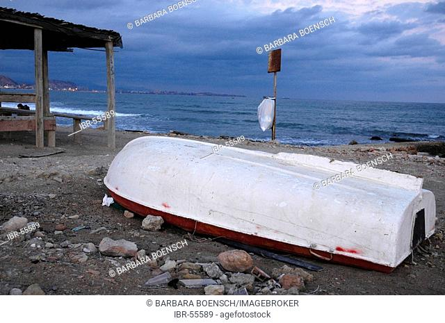 Old fishing boat lies overturned on the beach, Alicante, Costa Blanca, Spain