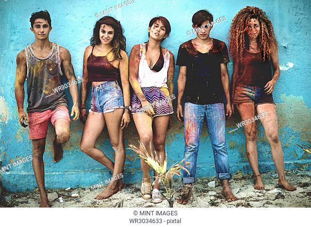 Five young people lined up against a wall covered in paint looking at camera