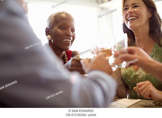 Smiling mature women drinking wine, dining at restaurant